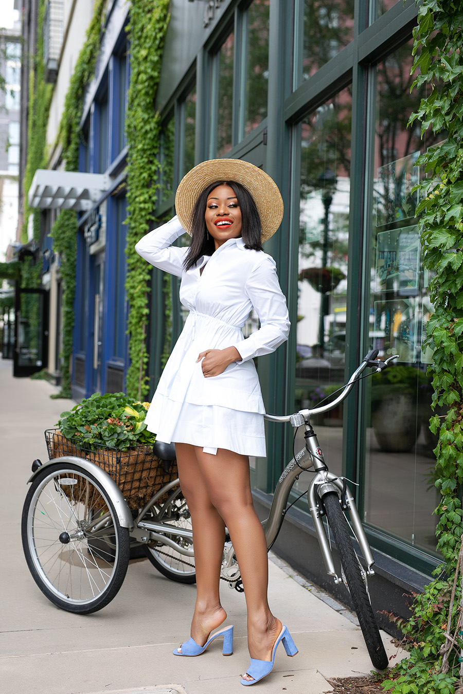 a girl in white dress and hat next to her bicycle
