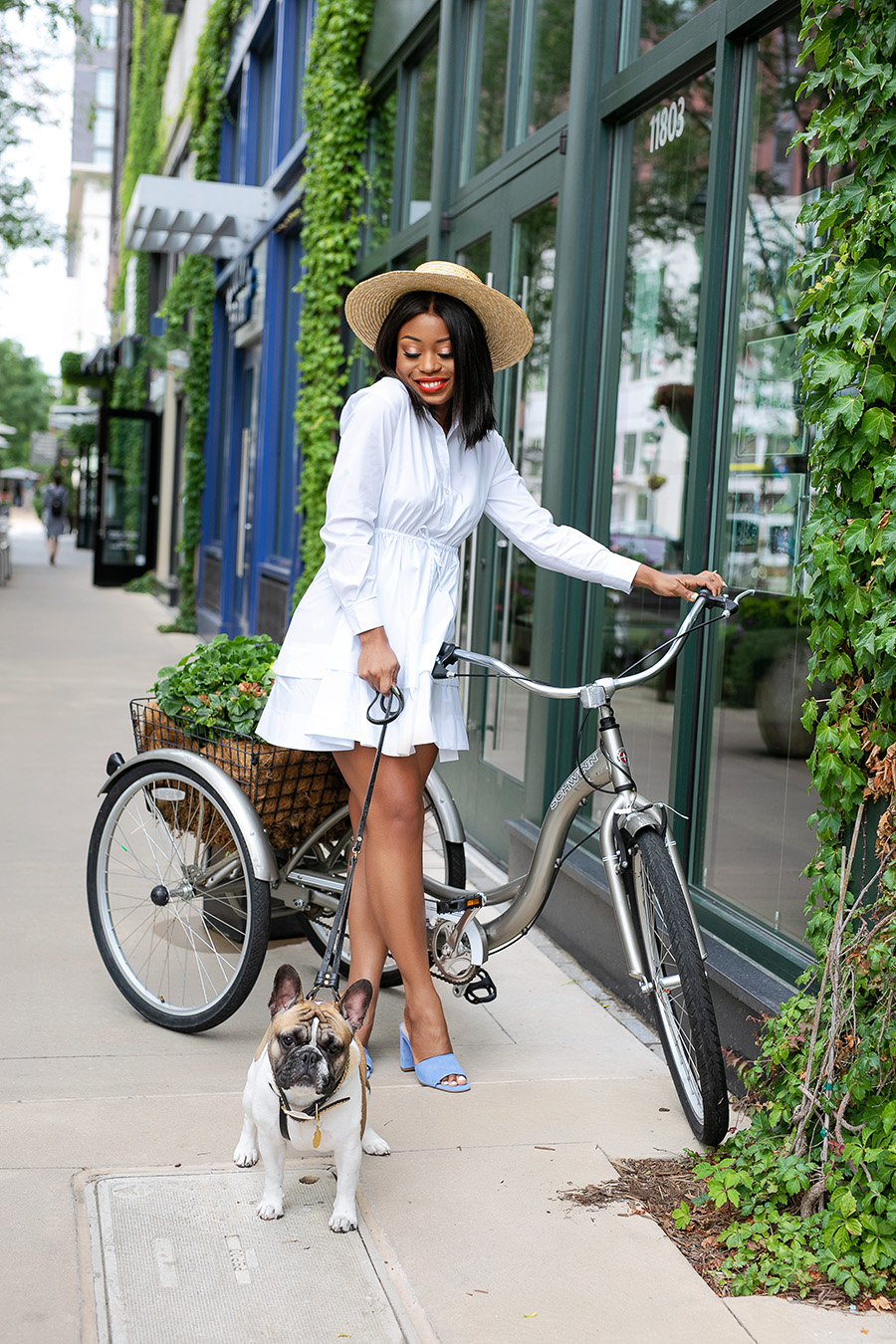 a girl in little white dress with her dog and bike