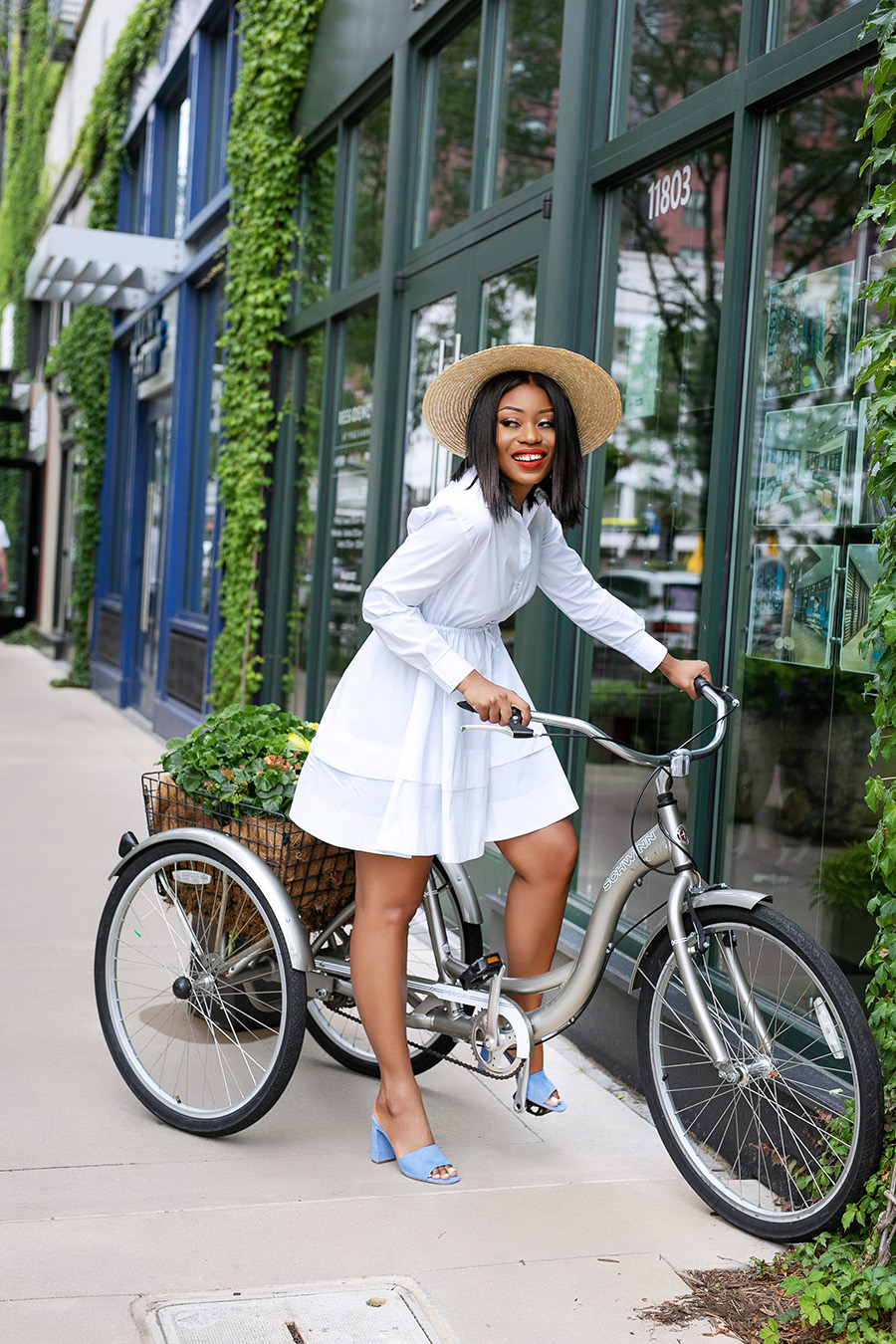 a girl in white dress with straw hat on the bike