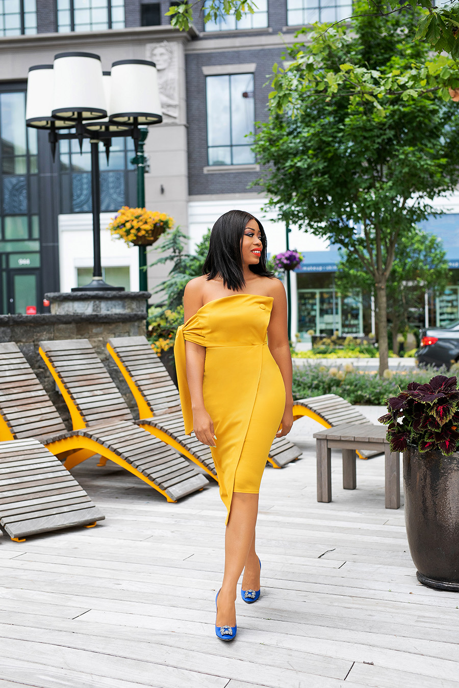 Yellow summer off shoulder dress and blue pumps in the city