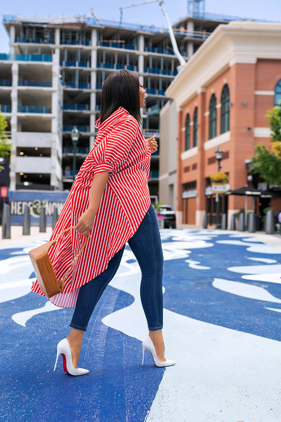 a girl walking away in red and white long summer stripe shirt with blue jeans