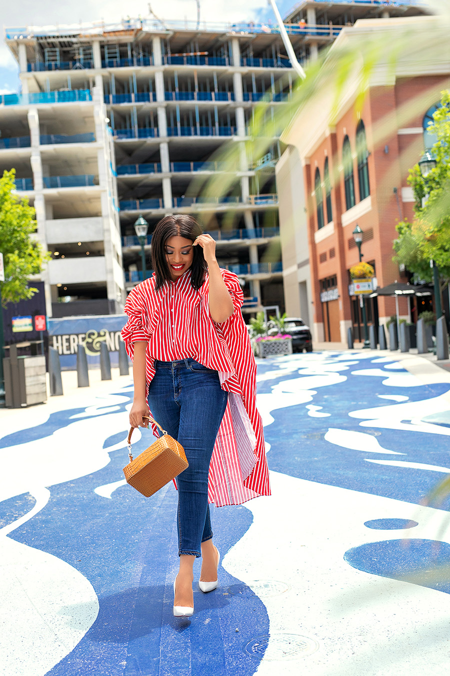 A girl in red and white long stripe shirt with blue jeans strolling in the city
